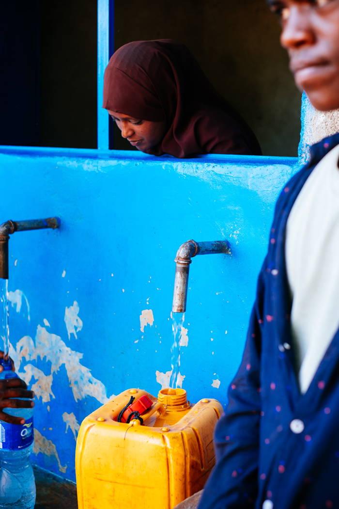 Die Wasserkioske sind täglich zwei Mal geöffnet. Für jeden Kiosk gibt es eine Person, die dort Verantwortung übernimmt und die Ausgabe des Wassers regelt.