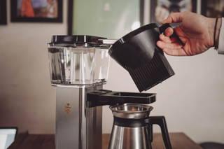 Setze nun den Filter zusammen mit dem Kaffee wieder in die Maschine. (Der Griff muss sich dabei rechts befinden)