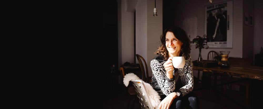 lächelnde Frau, die senkrecht auf dem Stuhl sitzt und eine Tasse Kaffee hält
