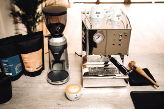 House Blend und Grano Gayo Espresso neben Graef Mühle und QuickMill Orione Espressomaschine und Cappuccino
