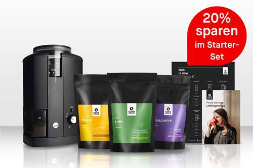 Drei farbenfrohe Kaffeebeutel und eine elektrische Kaffeemühle